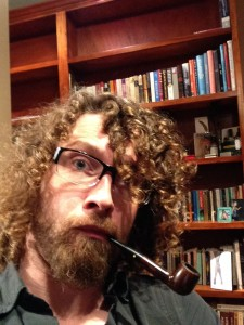 Promising Curmudgeon Poses before Large Staxks of Books with Pipe
